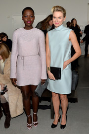 Lupita Nyong'o kept cozy in a pale-pink sweater dress by Calvin Klein Collection during the label's fashion show.
