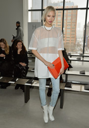 For a bit of color, Soo Joo Park accessorized with an oversized orange clutch.