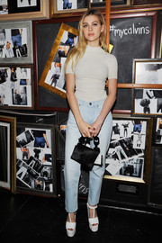 A black fur purse with a chunky chain strap topped off Nicola Peltz's ensemble.