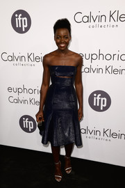 Lupita Nyong'o stayed on trend in silver skinny-strap sandals.