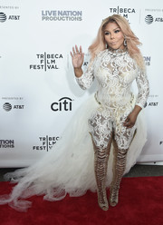 Lil Kim added extra oomph with a pair of gold thigh-high lace-up boots.