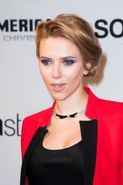 Scarlett Johansson went bold with color, sporting smoky blue eyeshadow and a bright red suit.