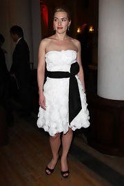 Kate wore a white cocktail dress with textured rosettes and a black bow sash for the Citizens Gala in London.