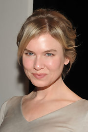 Renee Zellweger's messy updo at the Carlina Herrera runway show can be recreated with just a few bobby pins. Simply section out bangs and a few face-framing strands, pull the rest back, twist and pin into place.