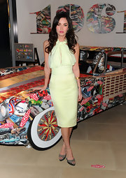 Megan Fox posed seductively at the Jaguar 50th Anniversary party in New York City. The sultry star wore a pale yellow chiffon dress with ankle strap peep-toe pumps. She puckered up with pink lips and her dark locks were worn in her signature curls.