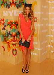 Jennifer paired her coral ruffled dress with a simple leather clutch.