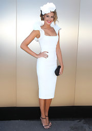 Laura Dundovic topped off her white sheath dress with black strappy sandals.