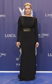 Kate wore a sleek black evening dress to show off her fab figure. The waist was belted with studs and she carried a hard case clutch to complete her dark look.