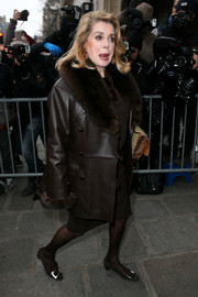 Catherine Deneuve joined the glam crowd during Paris Fashion Week wearing a brown fur-lapel leather coat.