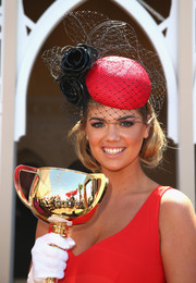 Kate Upton matched her dress with a rose-embellished red and black veiled hat during Melbourne Cup Day.
