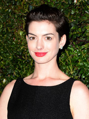 Anne Hathaway wore her short hair teased with a side part during the Chanel and Charles Finch pre-Oscar dinner.