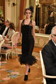 Lily-Rose Depp was all about flirty elegance in a little black dress with sheer shoulder straps and a layered tulle hem at the Chanel Collection des Métiers d'Art show.