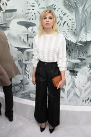 Cecile Cassel accessorized with an orange Chanel hard-case clutch for a pop of color to her monochrome outfit.