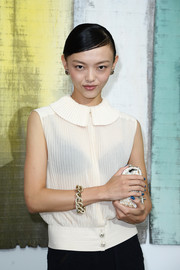 Rila Fukushima chose a vintage-looking pleated white blouse for the Chanel fashion show.