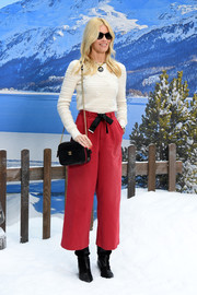 Claudia Schiffer styled her look with a black chain-strap bag by Chanel.