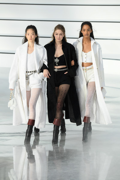 Gigi Hadid rocked a black tweed coat, crop-top, and hot pants combo at the Chanel Fall 2020 runway show.
