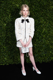 Lucy Boynton tied her look together with a quilted purse by Chanel.