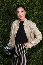 Michelle Yeoh attended the Charles Finch and Chanel pre-BAFTA dinner carrying a printed black clutch.