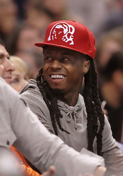Lil Wayne wore a bright red baseball cap for the Bobcats vs Heat basketball game.