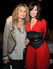 Gina Gershon topped of her red dress in fierce style with an oversized black leather belt at the Charlotte Ronson fashion show after-party.