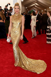 Kate Hudson was truly golden on the Met Gala red carpet wearing a figure-hugging gown with a mandarin collar and swooping train.