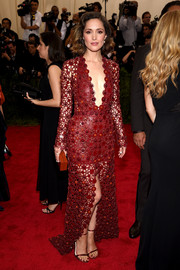 Rose Byrne attended the Met Gala looking edgy, sexy, and glamorous in equal parts in a hand-cut red Calvin Klein leather gown with a navel-grazing neckline and a high front slit.
