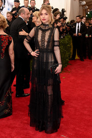 Imogen Poots wore a black long sleeve sheer gown with lace detail to the 2015 Met Gala.