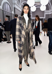 Caroline Issa arrived for the Chloe fashion show all bundled up in a fringed plaid coat.