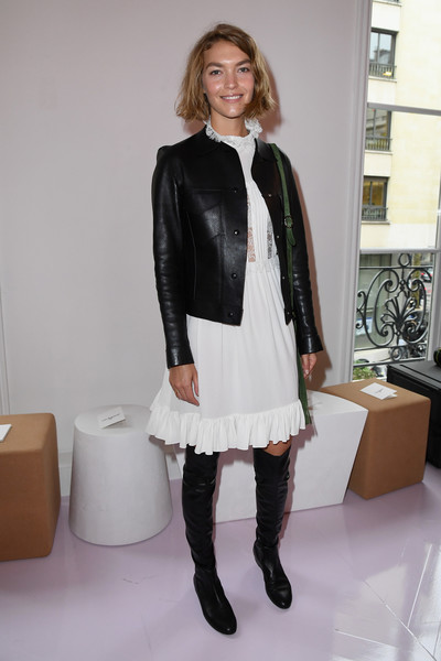 Arizona Muse contrasted her delicate frock with an edgy leather jacket.