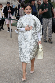 Miroslava Duma was vintage-glam in a white and silver floral brocade coat during the Chloe fashion show.