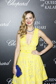 Petra Nemcova went for a striking mix of colors with this blue hard-case clutch and yellow dress combo at the 'Garden of Kalahari' movie presentation.