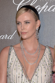 Charlize Theron amped up the glamour with layers of diamond necklaces.