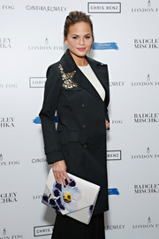 Chrissy Teigen showed off a charming oversized floral envelope clutch during the London Fog celebration.