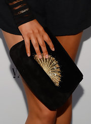 Chrissy accessorized her black ensemble with an oversize black clutch that featured a beaded sunburst design.