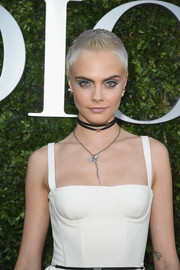 Cara Delevingne adorned her bare neckline with a cute sterling pendant and a pair of star chokers for the Christian Dior '70 Years of Creation' exhibition.