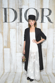Natalia Dyer topped off her dress with a black wool coat, also by Dior.
