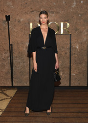 Karlie Kloss kept it understated in a black V-neck gown with flutter sleeves at the Dior Cruise 2020 show.