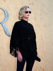 Charlize Theron attended the Christian Dior Cruise 2018 show looking Western-chic in a fringed suede jacket from the label.