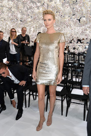 Charlize Theron radiated in a gold sequined mini dress by Christian Dior during the label's fashion show.