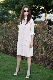 Olga Kurylenko layered a sleeveless pink coat over a white button-down for a casual-chic look during the Dior Couture fashion show.