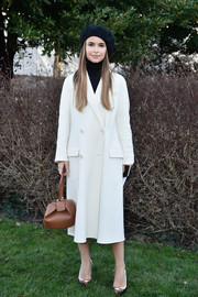 Miroslava Duma looked very Parisian-chic in a white double-breasted wool coat and a black beret at the Christian Dior Couture show.