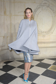 Leelee Sobieski cut a flirty silhouette in a gray flared-hem coat by Dior during the label's fashion show.