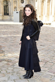 For her Dior show-going look, Lorde got all dolled up (without quite losing that signature edge of hers) in an ankle-length navy dress from the brand, featuring black ruffle detailing down the back.