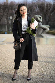 Kristina Bazan accessorized her look with a stylish black satchel, also by Dior.