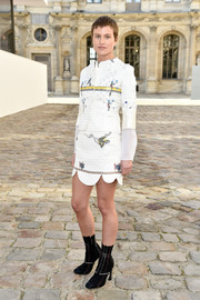 Olympia Scarry looked adorably chic at the Christian Dior fashion show in an embroidered white skirt suit with a scalloped hem.