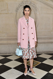 Caroline Issa layered a pink pea coat over a print dress for the Christian Dior fashion show.