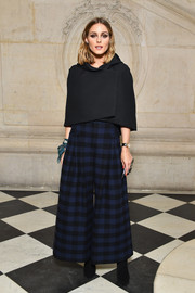 Olivia Palermo bundled up in a classic black capelet by Dior for the brand's Spring 2018 show.