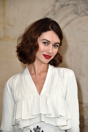 Olga Kurylenko attended the Christian Dior fashion show wearing her hair in a curled-out bob.