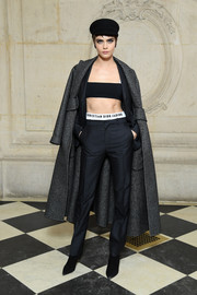 Cara Delevingne rocked a gray houndstooth coat, black suit, and bandeau top combo at the Dior Fall 2018 show.
