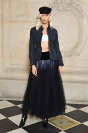 Karlie Kloss layered a fitted navy jacket by Dior over a white bandeau top for the label's Spring 2018 show.
